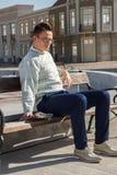 Hombre con los vidrios en la localización blanca del suéter en el ne del banco y de la tenencia Fotos de archivo libres de regalías