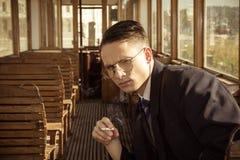 Hombre con los vidrios en un traje que se sienta en un tren de carromatos de madera viejo imágenes de archivo libres de regalías