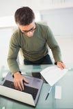 Hombre con los vidrios que lee el papel y que usa el ordenador portátil Fotos de archivo