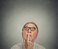Hombre con los vidrios que miran el fondo gris para arriba aislado fotografía de archivo