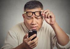 Hombre con los vidrios que tienen problema que ve el teléfono defender problemas de la visión Imagenes de archivo