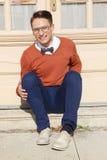 Hombre con los vidrios y el suéter que se sientan en pasos delante de la casa Imagenes de archivo
