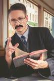 Hombre con los vidrios y las barbas en el traje que se sienta en un de madera viejo imagenes de archivo