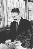 Hombre con los vidrios y las barbas en el traje que se sienta en un de madera viejo foto de archivo