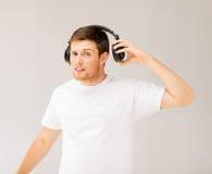 Hombre con música ruidosa que escucha de los auriculares Imagenes de archivo