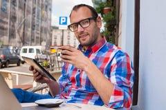 Hombre con PC de la tableta en café. Él está bebiendo el café. Foto de archivo libre de regalías