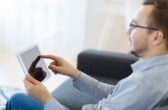 Hombre con PC de la tableta en casa Fotos de archivo libres de regalías