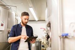 Hombre con PC de la tableta en la cervecería del arte o la planta de la cerveza foto de archivo