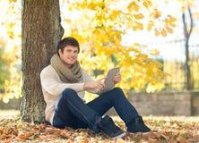 Hombre con PC de la tableta en parque del otoño Imágenes de archivo libres de regalías