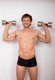 Hombre con pesas de gimnasia Foto de archivo