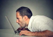 Hombre con problemas de la visión usando Internet de la ojeada del correo electrónico de la lectura del ordenador imagenes de archivo