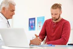 Hombre con problemas de salud que visita al urólogo foto de archivo