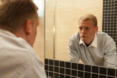 Hombre con resaca en un cuarto de baño Foto de archivo