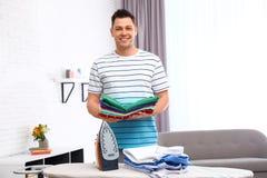 Hombre con ropa doblada cerca del tablero que plancha foto de archivo libre de regalías