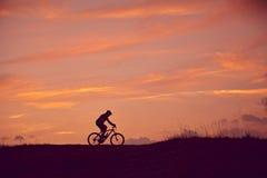 Hombre con salida del sol biking de la montaña imagenes de archivo