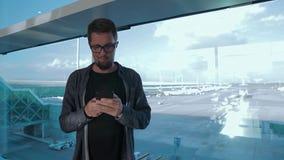 Hombre con smartphone en aeropuerto, solamente metrajes
