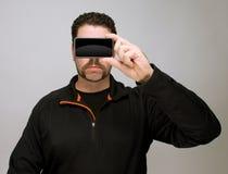 Hombre con smartphone por la cara Imágenes de archivo libres de regalías