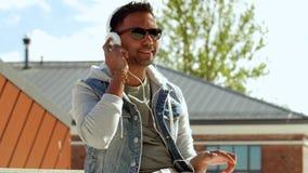 Hombre con smartphone y auriculares en el top del tejado almacen de metraje de vídeo