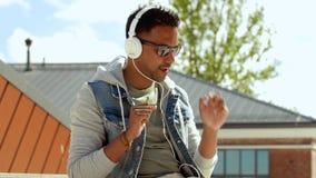 Hombre con smartphone y auriculares en el top del tejado metrajes