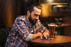 Hombre con smartphone y cerveza que manda un SMS en la barra Fotos de archivo libres de regalías