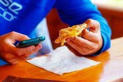 Hombre con smartphone y pizza en manos Foto de archivo libre de regalías