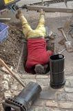 Hombre con su cabeza abajo de un agujero en el camino foto de archivo