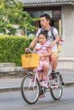 Hombre con su hija en una bici de alquiler Pekín, China Imágenes de archivo libres de regalías