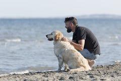 Hombre con su perro en una playa Imagen de archivo libre de regalías