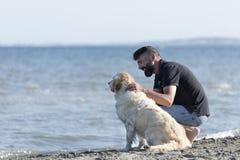Hombre con su perro en una playa Fotografía de archivo libre de regalías