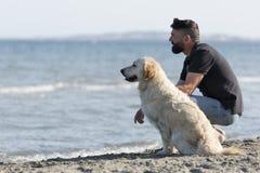 Hombre con su perro en una playa Fotografía de archivo