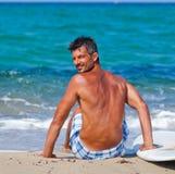 Hombre con su tabla hawaiana en la playa Imágenes de archivo libres de regalías