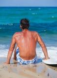 Hombre con su tabla hawaiana en la playa Imagen de archivo