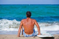 Hombre con su tabla hawaiana en la playa Foto de archivo libre de regalías