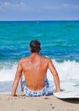 Hombre con su tabla hawaiana en la playa Foto de archivo