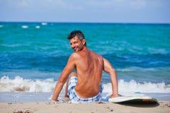 Hombre con su tabla hawaiana en la playa Fotos de archivo libres de regalías