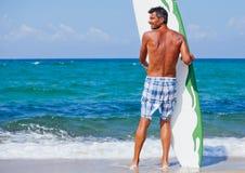 Hombre con su tabla hawaiana en la playa Fotos de archivo