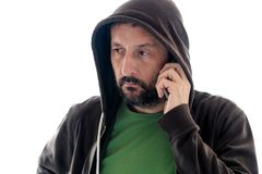 Hombre con sudadera con capucha usando el teléfono móvil imagen de archivo