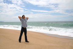 Hombre con sus manos detrás de la pista en la playa Imagenes de archivo