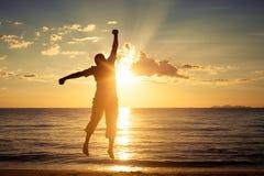 Hombre con sus manos para arriba en el tiempo de la puesta del sol Imagenes de archivo