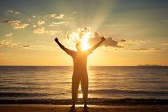 Hombre con sus manos para arriba en el tiempo de la puesta del sol Foto de archivo