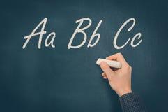 Hombre con tiza que escribe las letras de ABC en la pizarra Imagen de archivo libre de regalías