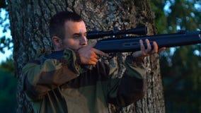 Hombre con un arma en la caza detrás de un árbol lento almacen de metraje de vídeo