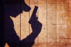 Hombre con un arma en sombra en un fondo de madera Imagenes de archivo