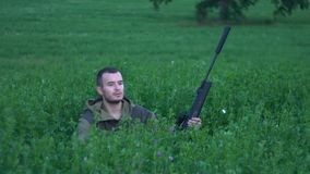 Hombre con un arma que se sienta en la hierba alta almacen de metraje de vídeo