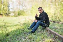 Hombre con un cigarrillo y una botella fotografía de archivo