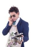 Hombre con un delantal que sostiene un pote de cocinar y que habla sobre el teléfono foto de archivo