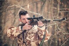 Hombre con un francotirador y un tiroteo en una estación abierta, mirando con alcance Fotografía de archivo