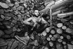 Hombre con un hacha cerca de la acción de la leña Imágenes de archivo libres de regalías