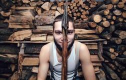 Hombre con un hacha cerca de la acción de la leña Fotografía de archivo