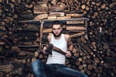 Hombre con un hacha cerca de la acción de la leña Imagen de archivo libre de regalías